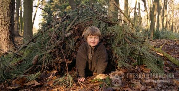 ребёнок в укрытии из веток